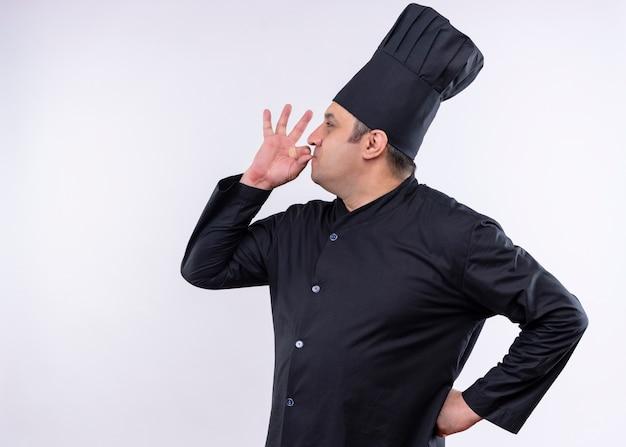 黒の制服を着て、白い背景の上においしい立っているための兆候を示す帽子を調理する男性シェフ