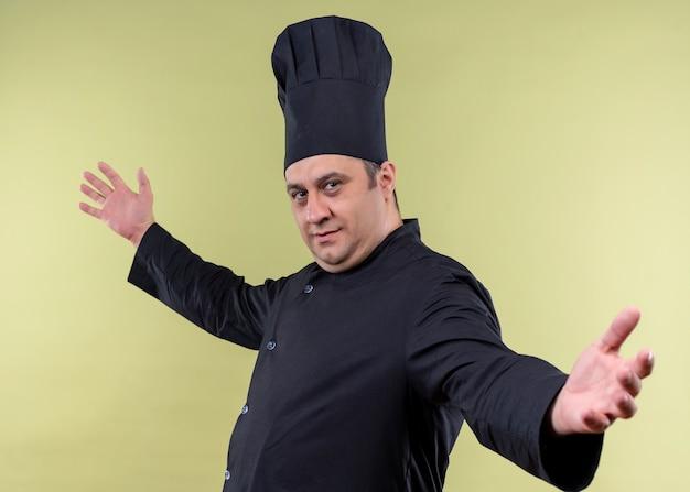 남성 요리사는 검은 색 유니폼을 입고 모자를 요리하고 녹색 배경 위에 서있는 환영 제스처를 만드는 미소를 짓습니다.