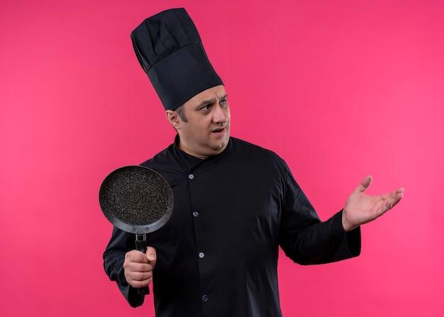 黒の制服を着て、ピンクの背景の上に立っている帽子を調理する男性シェフ