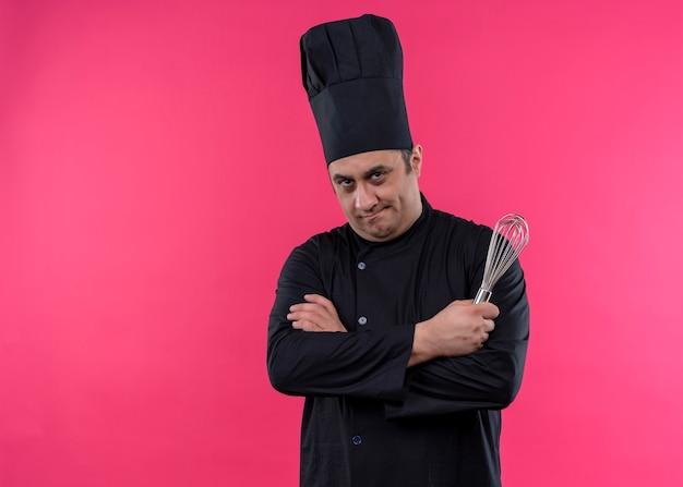 Cuoco unico maschio che indossa l'uniforme nera e cappello da cuoco che tiene la corolla che guarda l'obbiettivo con la faccia seria con le braccia incrociate in piedi su sfondo rosa