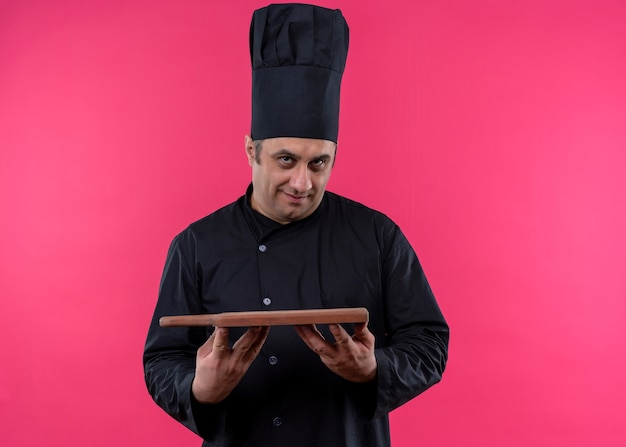 Cuoco unico maschio che indossa l'uniforme nera e cappello da cuoco che tiene il tagliere di legno cercando fiducioso in piedi su sfondo rosa