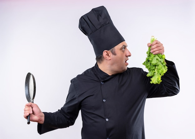 Male chef cook wearing black uniform and cook hat holding fresh lettuce and pan looking aside surprised standing over white background
