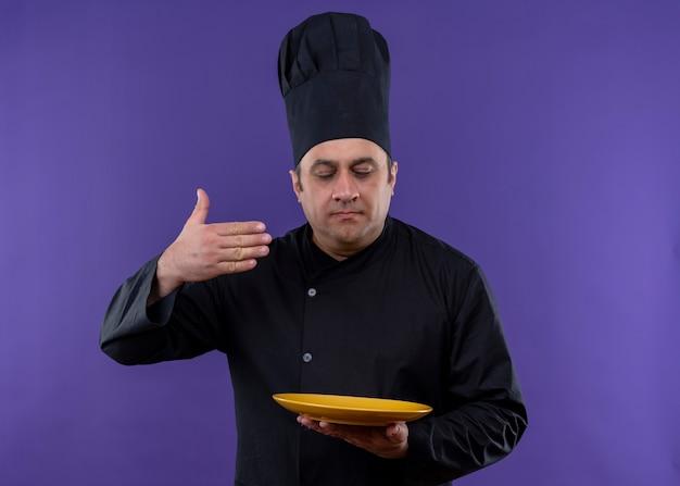 Cuoco unico maschio che indossa l'uniforme nera e cappello da cuoco che tiene la padella sentendo un odore gradevole di cibo gustoso in piedi su sfondo viola