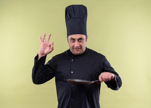 Cuoco unico maschio che indossa l'uniforme nera e cappello da cuoco che tiene la padella che mostra il segno giusto che sorride in piedi sopra il fondo verde