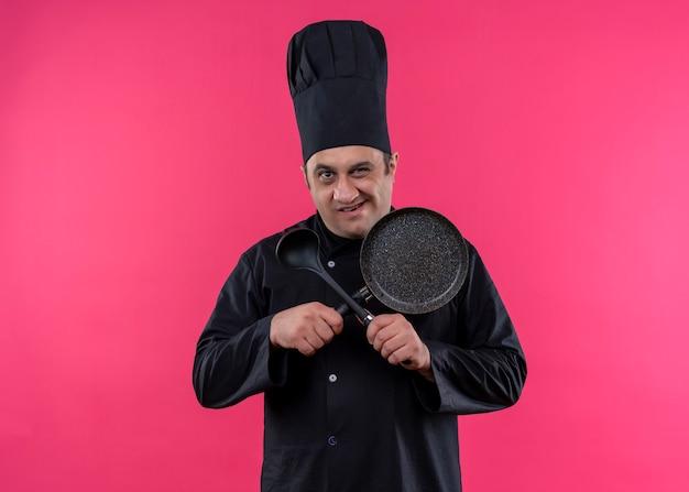 Cuoco unico maschio che indossa l'uniforme nera e cappello da cuoco che tiene la padella e il cucchiaio che attraversano le mani guardando la fotocamera con il sorriso in piedi su sfondo rosa