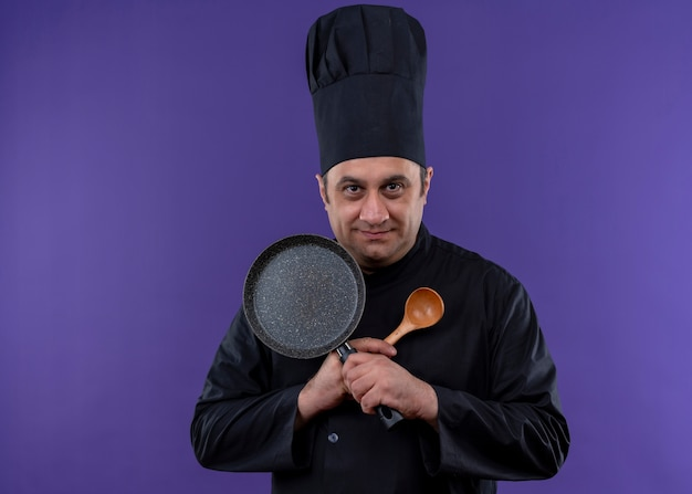 Male chef cook wearing black uniform and cook hat holding frying pan and wooden spoon crossing hands looking at camera smiling standing over purple background