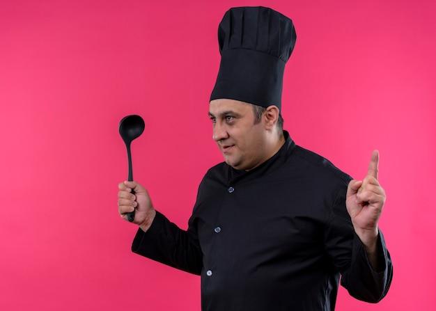 Cuoco unico maschio che indossa l'uniforme nera e cappello da cuoco che tiene il mestolo che osserva da parte mostrando il dito indice con la faccia seria che sta sopra il fondo rosa