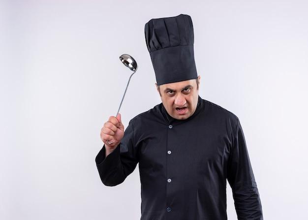 Cuoco unico maschio che indossa l'uniforme nera e cappello da cuoco che tiene il mestolo che guarda l'obbiettivo con la faccia arrabbiata che sta sopra fondo bianco