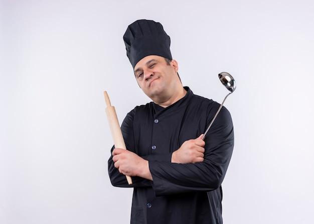Cuoco unico maschio che indossa l'uniforme nera e cappello da cuoco che tiene mestolo e mattarello ammiccanti e sorridenti guardando la fotocamera in piedi su sfondo bianco