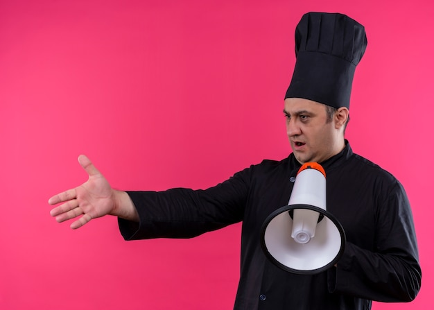 Male chef cook wearing black uniform and cook hat holding megaphone with arm out as asking question standing over pink background