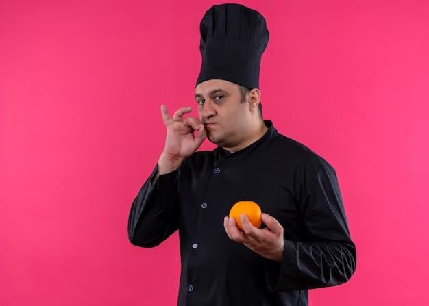 Cuoco unico maschio che indossa l'uniforme nera e cappello da cuoco che tiene la frutta arancione che mostra il segno per una condizione deliziosa sopra fondo rosa