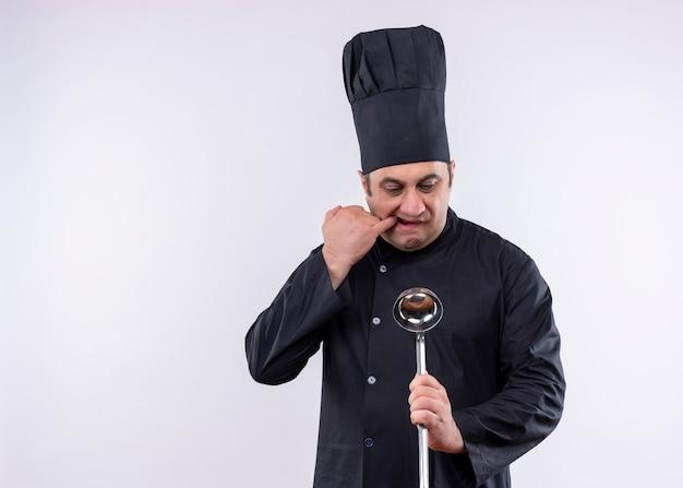 Cuoco unico maschio che indossa l'uniforme nera e cappello da cuoco che tiene la pagaia nervosa e preoccupata in piedi su sfondo bianco
