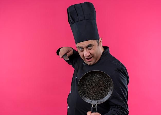 Cuoco unico maschio che indossa l'uniforme nera e cappello da cuoco che tiene la padella e il coltello che guarda l'obbiettivo con la faccia seria che sta sopra il fondo rosa
