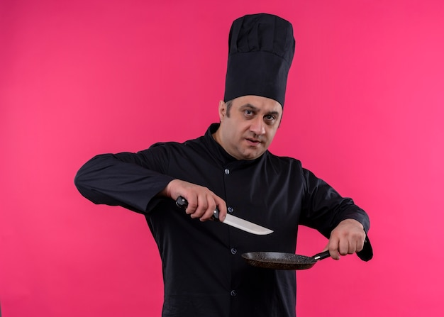 Male chef cook wearing black uniform and cook hat holding pan and knife looking at camera with serious face standing over pink background