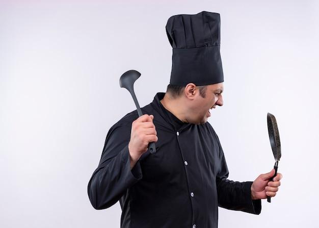 Cuoco unico maschio che indossa l'uniforme nera e cappello da cuoco che tiene la padella e il mestolo che grida con la faccia molto arrabbiata che sta sopra fondo bianco