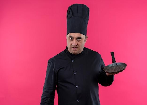 Cuoco unico maschio che indossa l'uniforme nera e cappello da cuoco che tiene una padella che osserva da parte sorpreso in piedi su sfondo rosa