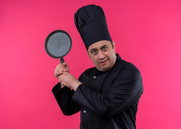 Male chef cook wearing black uniform and cook hat holding a pan looking at camera confused standing over pink background