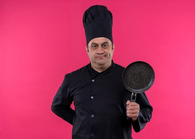 Cuoco unico maschio che indossa l'uniforme nera e cappello da cuoco che tiene una padella che guarda l'obbiettivo con espressione sicura in piedi su sfondo rosa