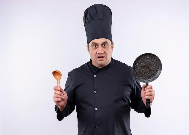Cuoco unico maschio che indossa l'uniforme nera e cappello da cuoco che tiene la padella e il cucchiaio di legno che guarda l'obbiettivo sorpreso in piedi su sfondo bianco