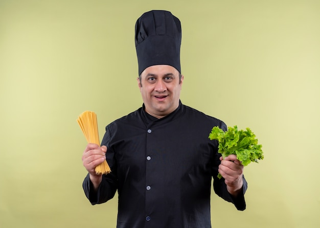 Male chef cook wearing black uniform and cook hat holding raw spaghetti and fresh lettuce looking happy and surprised standing over green background