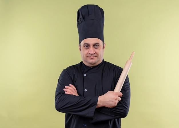 Cuoco unico maschio che indossa l'uniforme nera e cappello da cuoco che tiene il mattarello guardando la fotocamera con le braccia incrociate in piedi su sfondo verde
