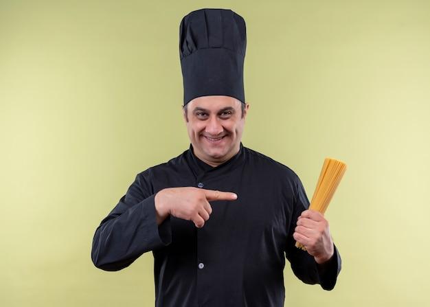Cuoco unico maschio che indossa l'uniforme nera e cappello da cuoco che tiene gli spaghetti di fila che indica con il dito che guarda l'obbiettivo sorridente in piedi su sfondo verde