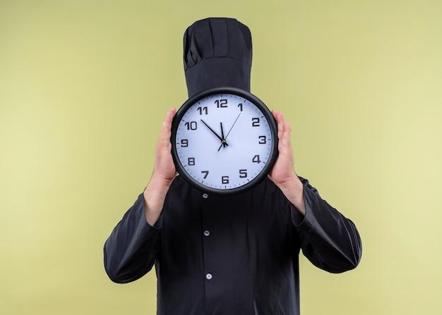 Cuoco unico maschio che indossa l'uniforme nera e cappello da cuoco che tiene l'orologio da parete che nasconde il suo volto dietro in piedi su sfondo verde