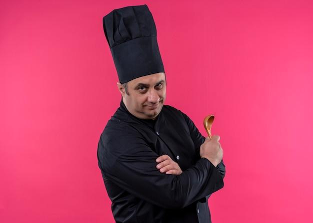 Cuoco unico maschio che indossa l'uniforme nera e cappello da cuoco che tiene il cucchiaio di legno che guarda l'obbiettivo con espressione fiduciosa in piedi su sfondo rosa