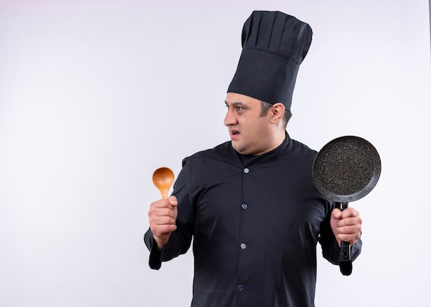 Male chef cook wearing black uniform and cook hat holding wooden spoon and pan looking aside surprised standing over white background
