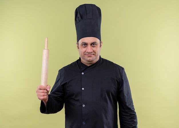 Cuoco unico maschio che indossa l'uniforme nera e il mattarello del holdung del cappello del cuoco che guarda l'obbiettivo con l'espressione sicura che sta sopra fondo verde