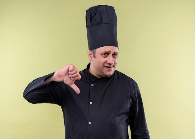 Cuoco unico maschio che indossa l'uniforme nera e cappello da cuoco che guarda l'obbiettivo scontento che mostra i pollici giù in piedi su sfondo verde