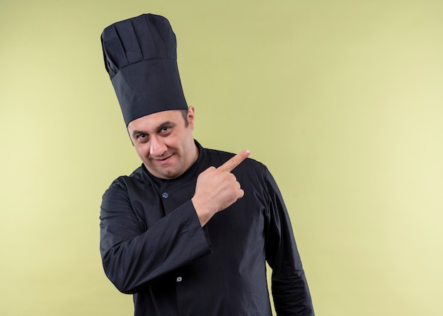 Cuoco unico maschio che indossa l'uniforme nera e cappello da cuoco che guarda l'obbiettivo sorridendo allegramente indicando con il dito indice di lato in piedi su sfondo verde