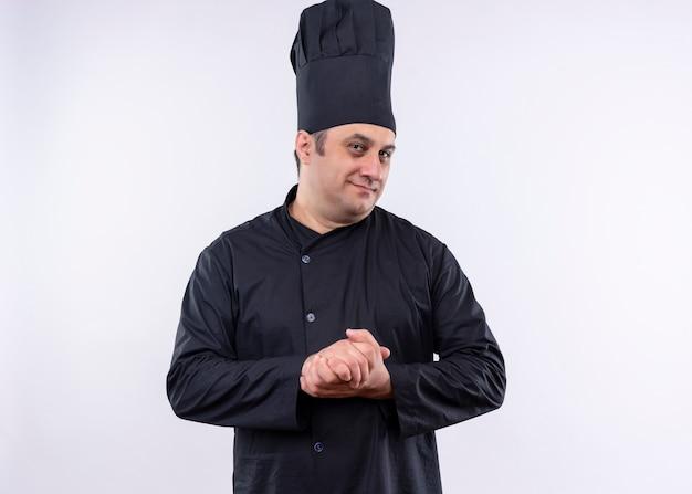 Cuoco unico maschio che indossa l'uniforme nera e cappello da cuoco che guarda l'obbiettivo sorridente strofinando le mani in piedi su sfondo bianco