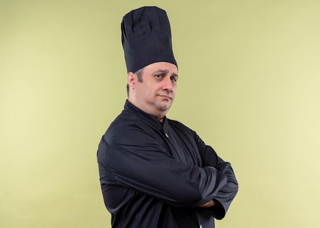 Cuoco unico maschio che indossa l'uniforme nera e cappello da cuoco che guarda l'obbiettivo con espressione seria fiduciosa con le braccia incrociate sul petto in piedi su sfondo verde