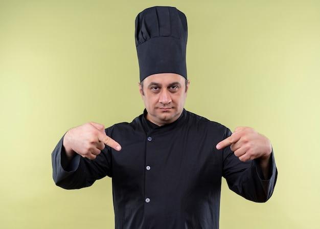 Cuoco unico maschio che indossa l'uniforme nera e cappello da cuoco guardando fiducioso che punta con le dita a se stesso in piedi su sfondo verde