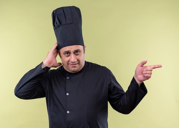 Cuoco unico maschio che indossa l'uniforme nera e cappello da cuoco che sembra confuso indicando con il dito di lato in piedi su sfondo verde