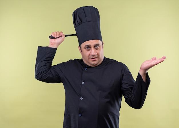 Cuoco unico maschio che indossa l'uniforme nera e cappello da cuoco che sembra confuso grattandosi la testa con il mestolo in piedi su sfondo verde
