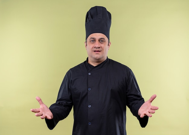 Male chef cook wearing black uniform and cook hat looking displeased holding arms out as asking question standing over green background