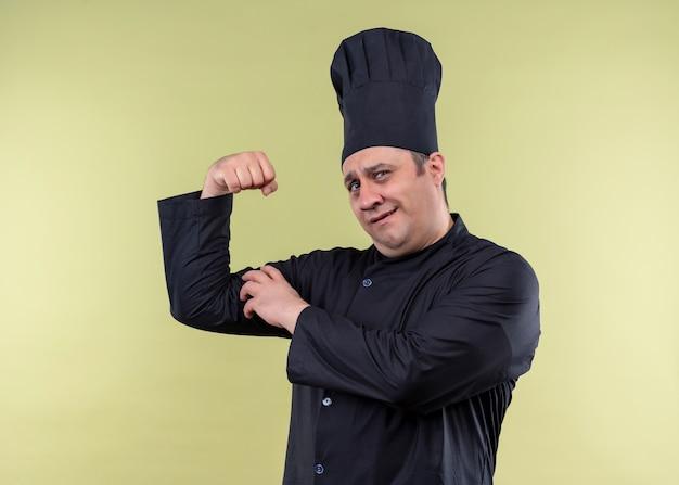 Cuoco unico maschio che indossa l'uniforme nera e cappello da cuoco che alza il pugno che mostra i bicipiti che sembrano fiduciosi in piedi su sfondo verde