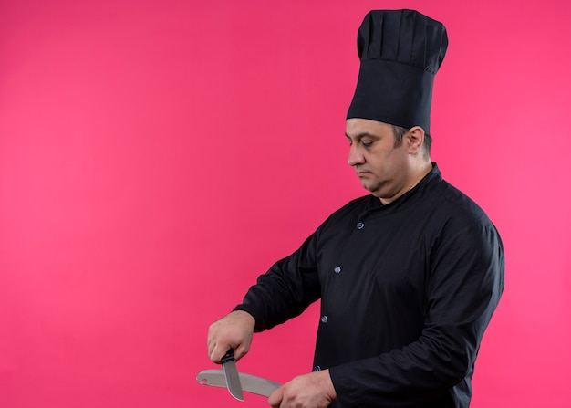 Cuoco unico maschio che indossa l'uniforme nera e coltelli per affilare il cappello da cuoco con la faccia seria in piedi su sfondo rosa