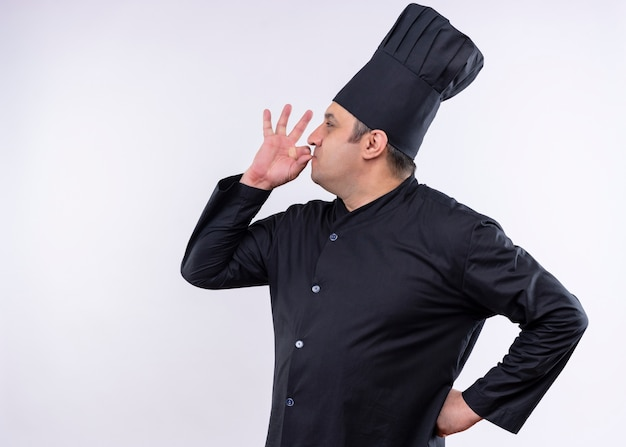 Male chef cook wearing black uniform and cook hat showing sign for delicious standing over white background