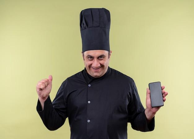 Cuoco unico maschio che indossa l'uniforme nera e cappello da cuoco che mostra il pugno di serraggio dello smartphone eccitato e felice in piedi su sfondo verde