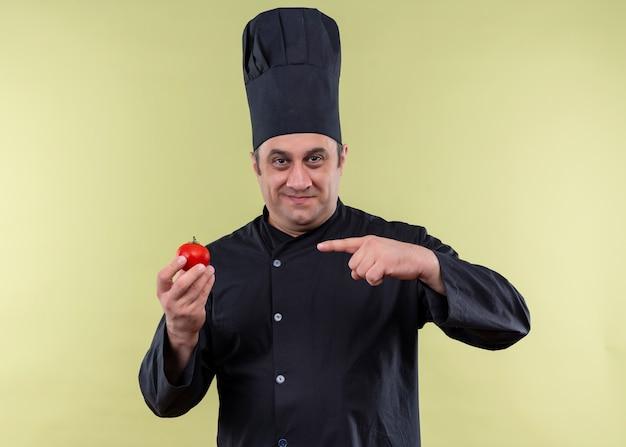 Cuoco unico maschio che indossa l'uniforme nera e cappello da cuoco che mostra il pomodoro che punta con il dito ad esso sorridendo guardando la fotocamera in piedi su sfondo verde