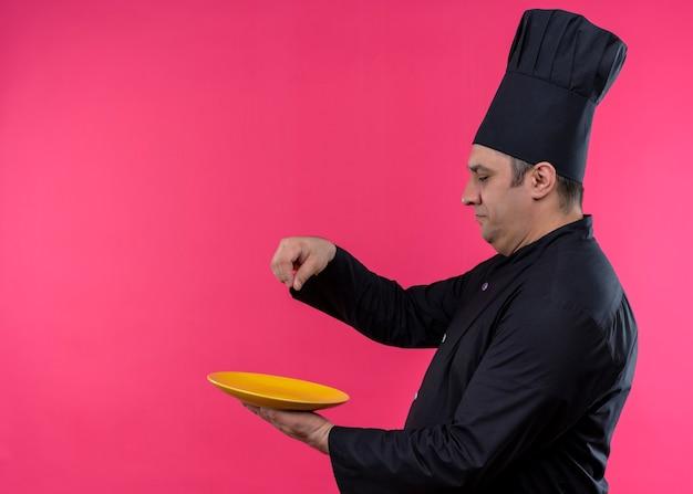 Cuoco unico maschio che indossa l'uniforme nera e cappello da cuoco spolverando di sale sul piatto con la faccia seria in piedi su sfondo rosa