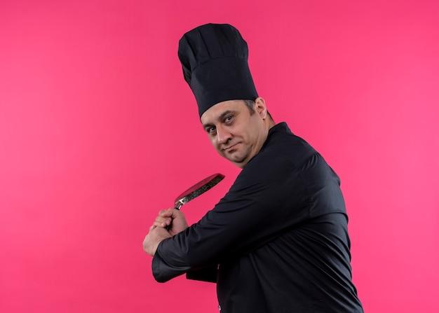 Cuoco unico maschio che indossa l'uniforme nera e cappello da cuoco che oscilla una padella che guarda l'obbiettivo sorridente in piedi su sfondo rosa