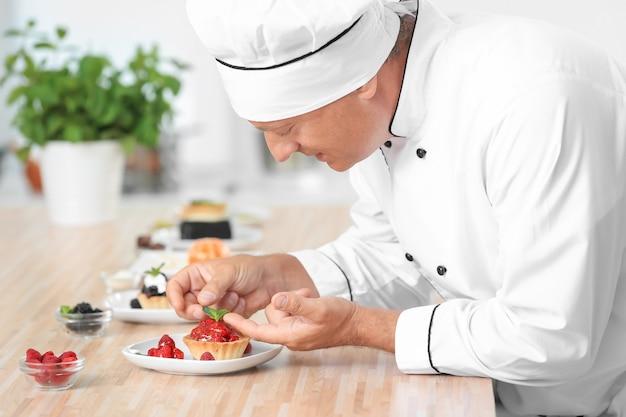Мужской шеф-повар готовит десерт на кухне