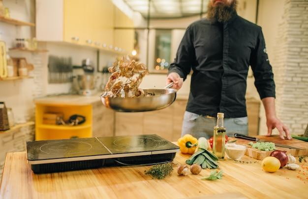 Шеф-повар-мужчина готовит мясо с овощами на сковороде