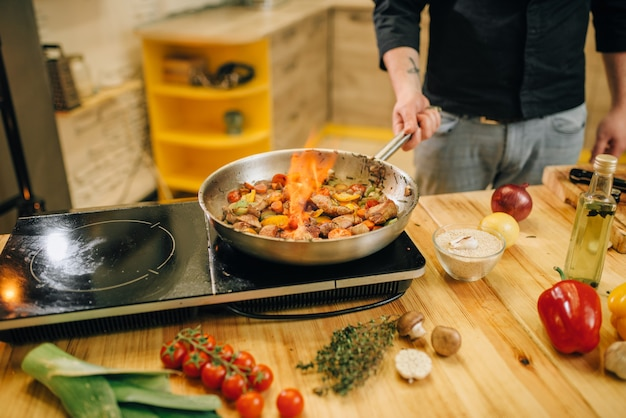 Шеф-повар-мужчина готовит мясо с овощами на огне