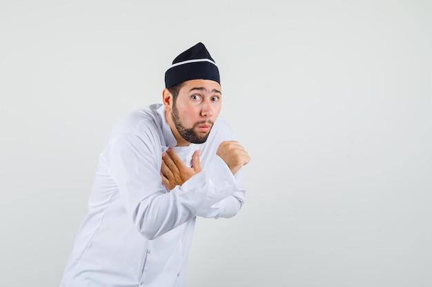 흰색 제복을 입고 기침을 하고 아픈 모습을 보이는 남성 요리사. 전면보기.