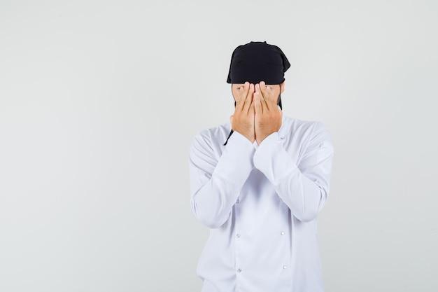 남자 요리사는 흰색 제복을 입은 손으로 얼굴을 가리고 겁에 질린 표정을 짓고 있습니다. 전면보기.